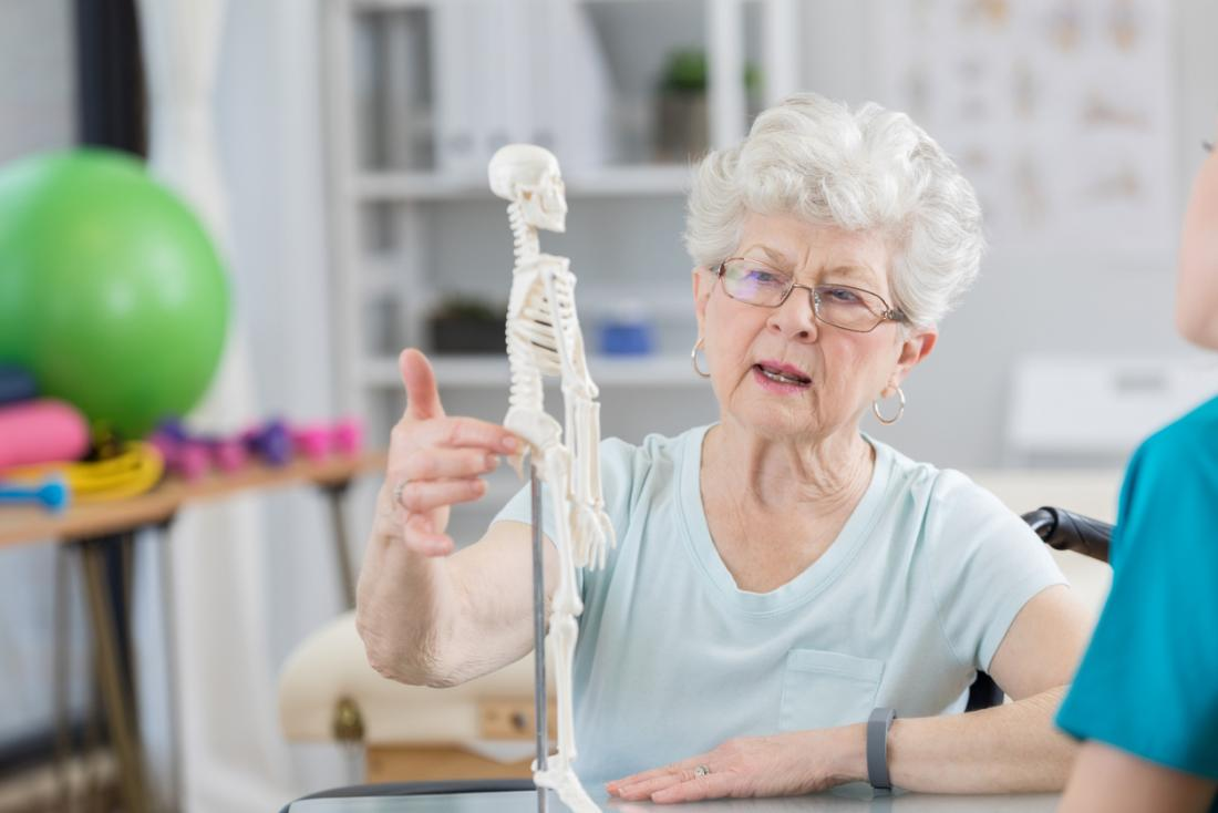 Senior woman talking to osteopath and chiropractor, pointing to model of skeleton to describe her pain.