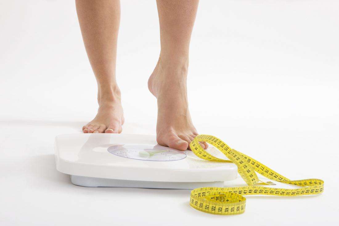 A woman on scales with a measuring tape