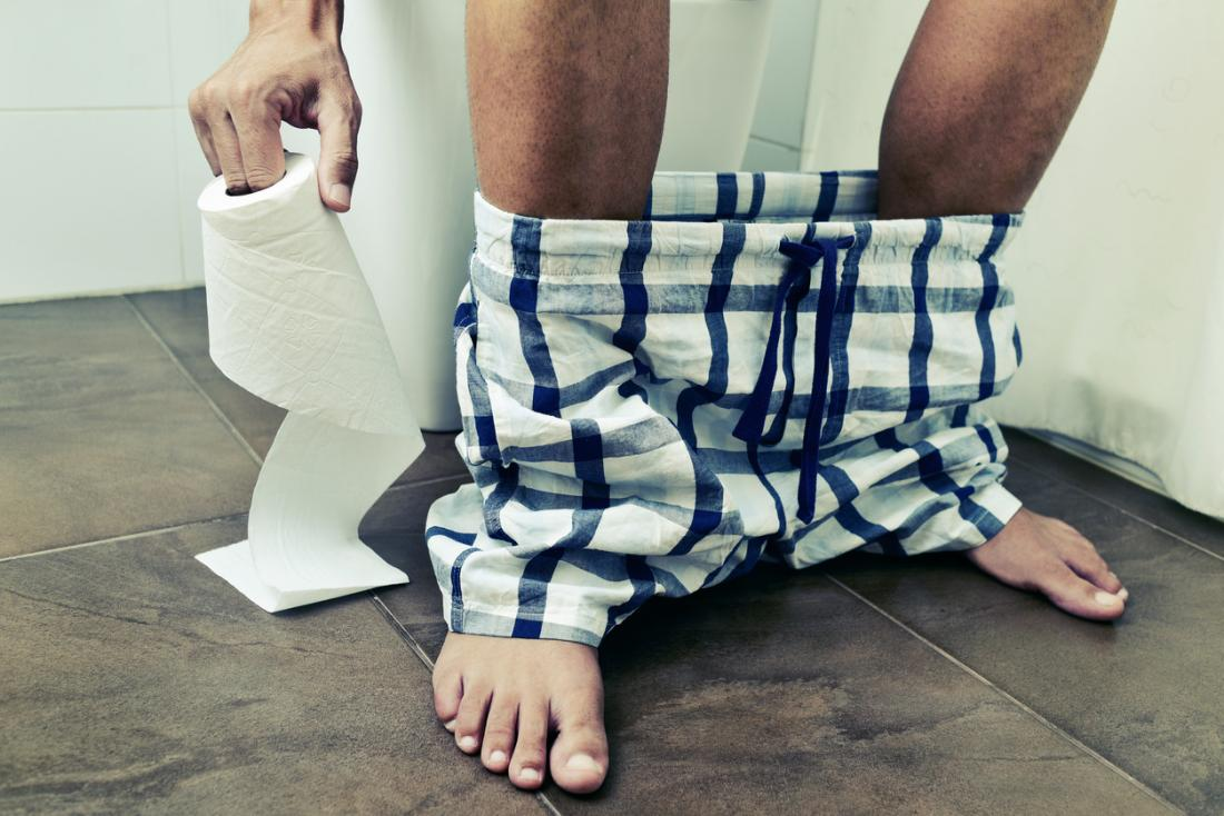Man sitting on toilet, reaching for toilet roll.
