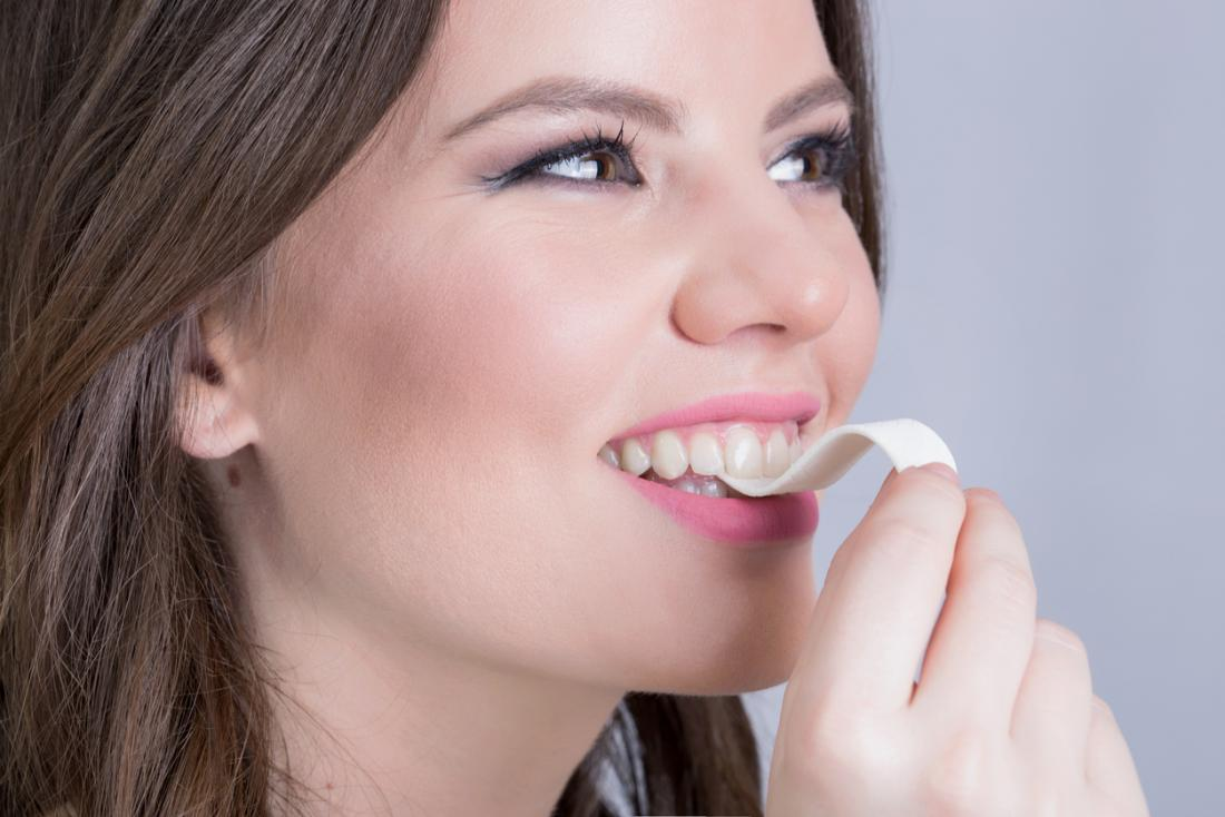 girl about to eat strip of chewing gum