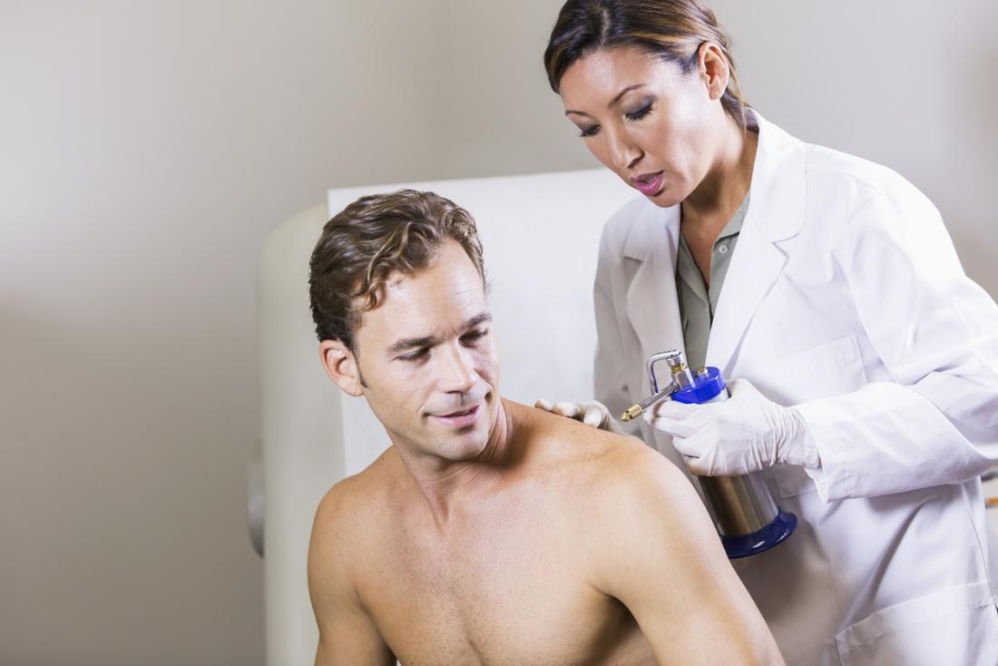 physician performing cryotherapy on man's shoulder
