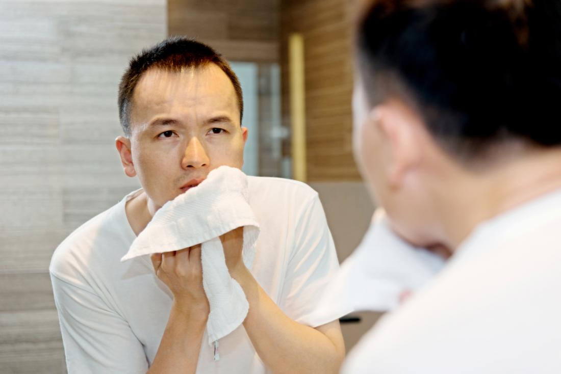 Young asian man washing and drying his face with towel to get rid of boil.