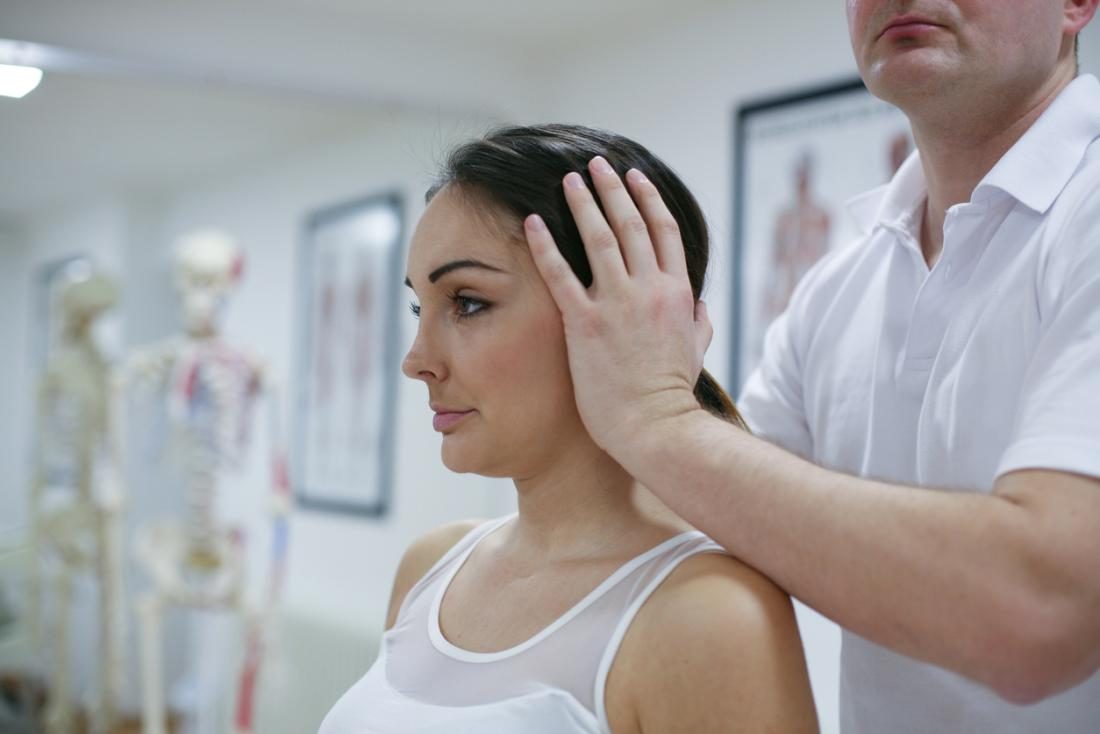 Woman having her head and neck manipulated by chiropractor.