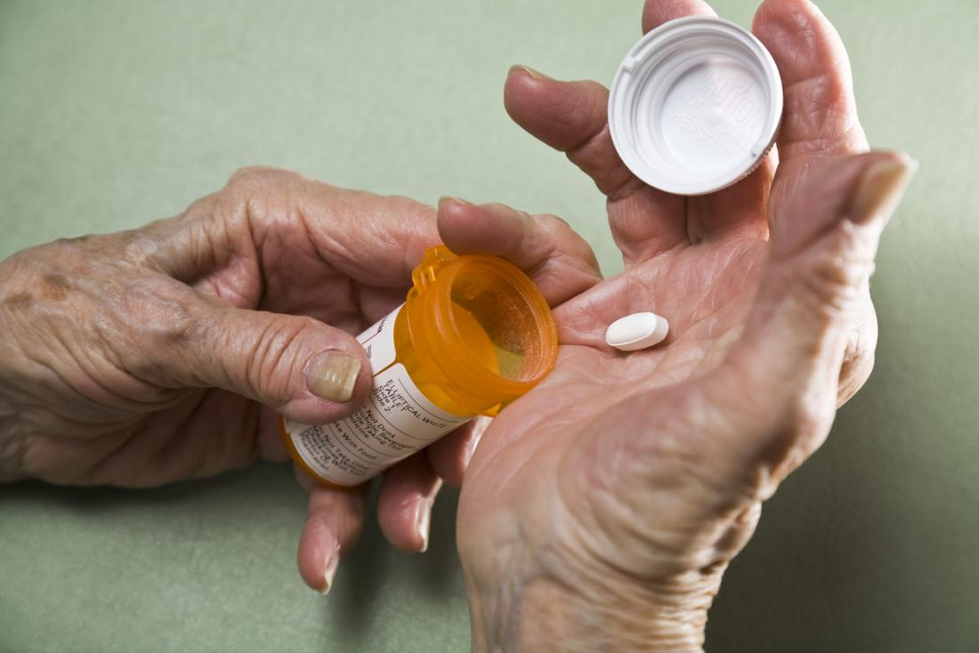 Person with arthritis, with medicine pill in palm from prescription drug pot.
