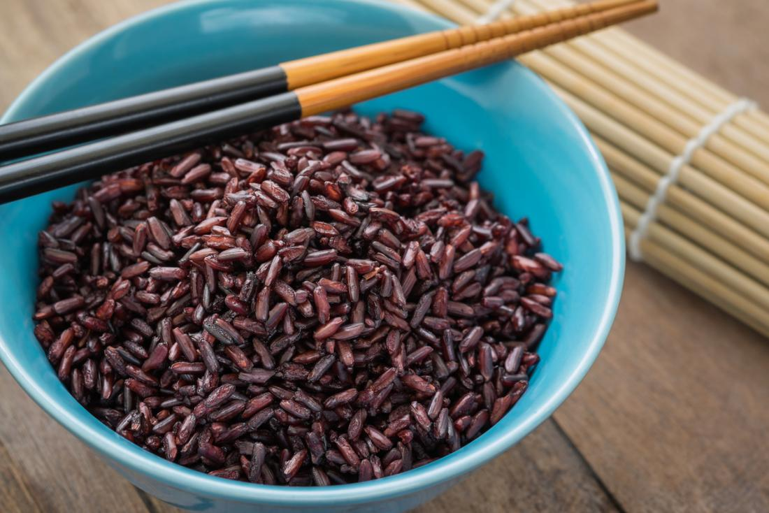Steamed purple and black rice in a bowl with chopsticks.