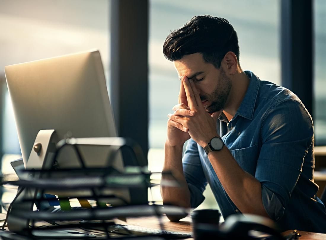 Man sitting at desk at work stressed and tired