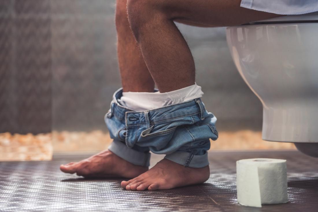 Man sitting on toilet.