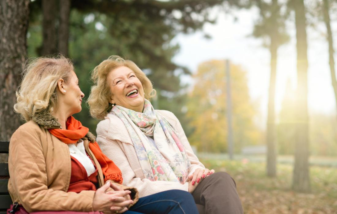 Two mature woman sitting on a bench in a park laughing