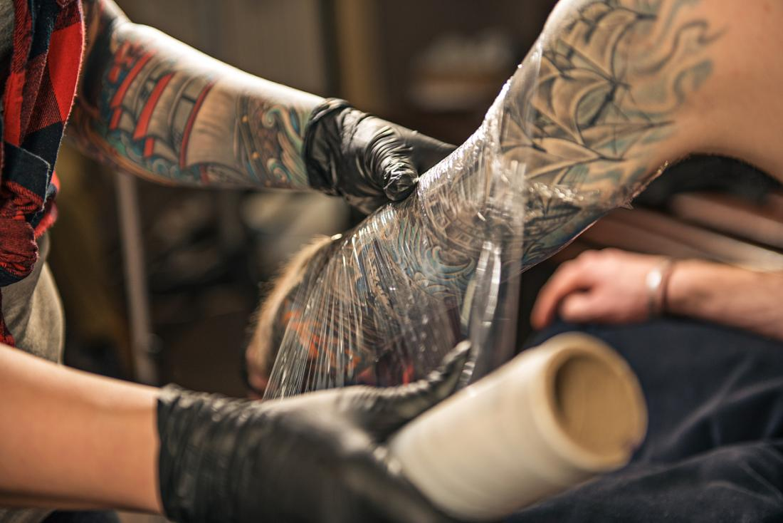 Tattoo artist wrapping client's arm in plastic clingfilm to encourage tattoo healing.