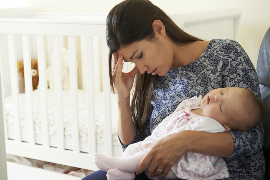 Woman with postpartum depression holding baby