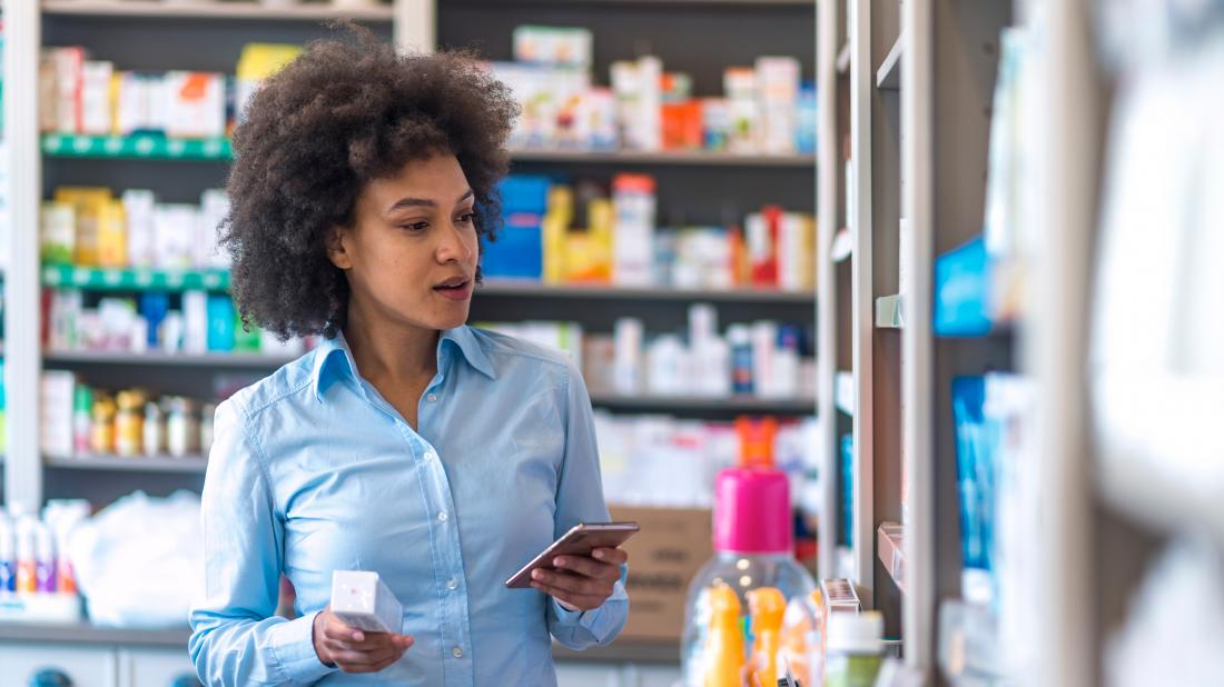 a woman in a pharmacy looking for a product that may treat canker sores