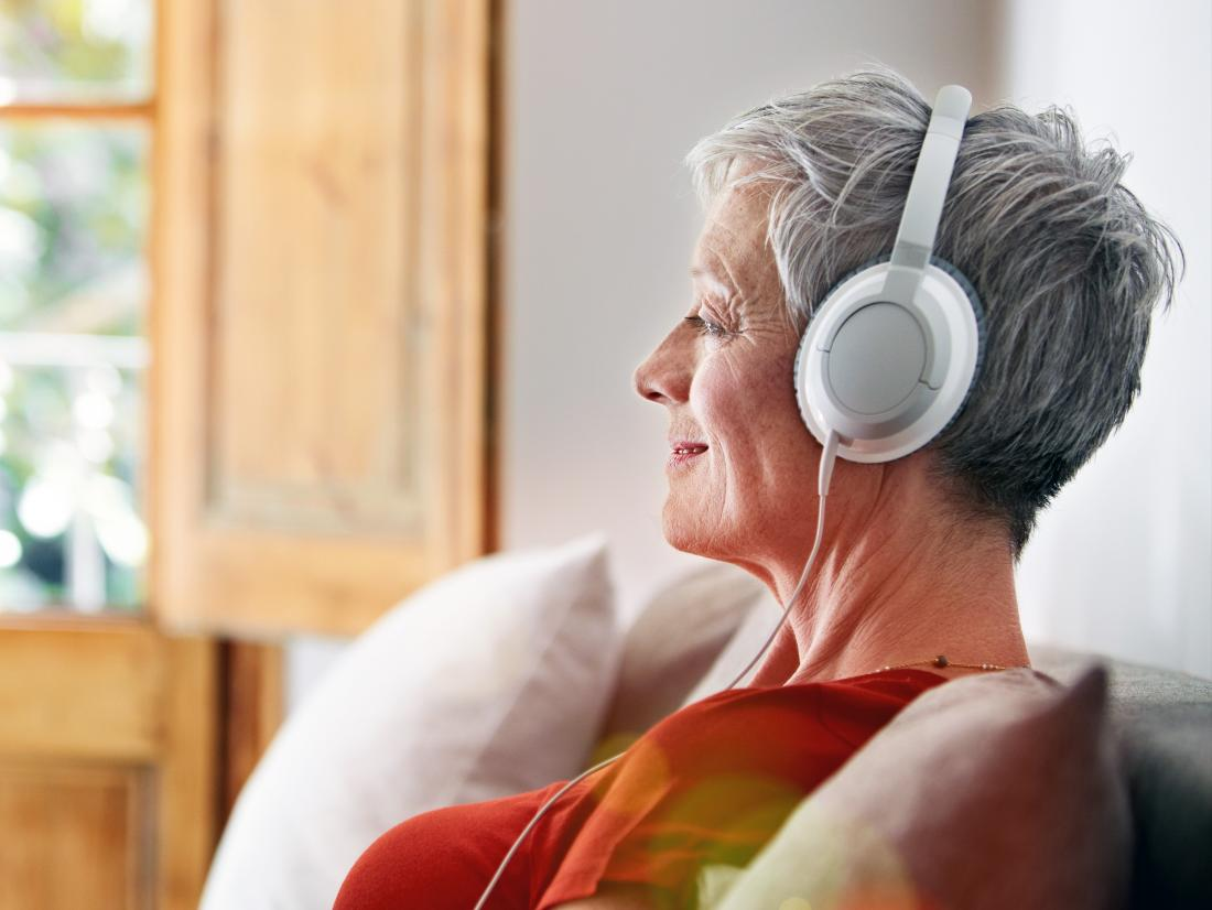 a woman listening to a binaural beats recording on headphones