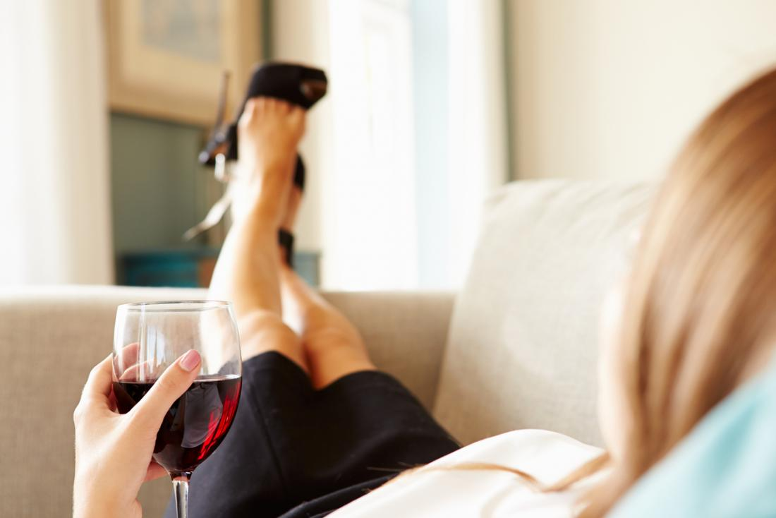 a woman laying on the sofa with a glass of wine