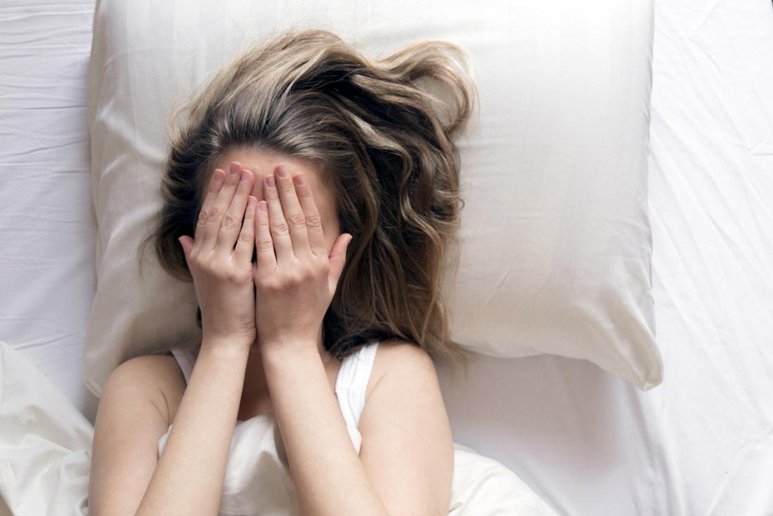 woman in bed covering her face with her hands