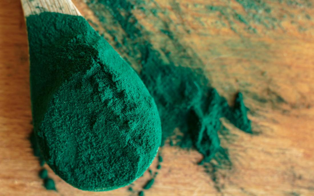 Chlorella or Spirulina powder on a wooden background
