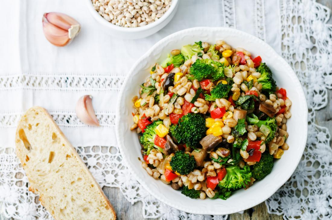 Barley porridge with corn, broccoli, garlic, mushrooms and pepper in a healthy vegetarian and vegan meal.