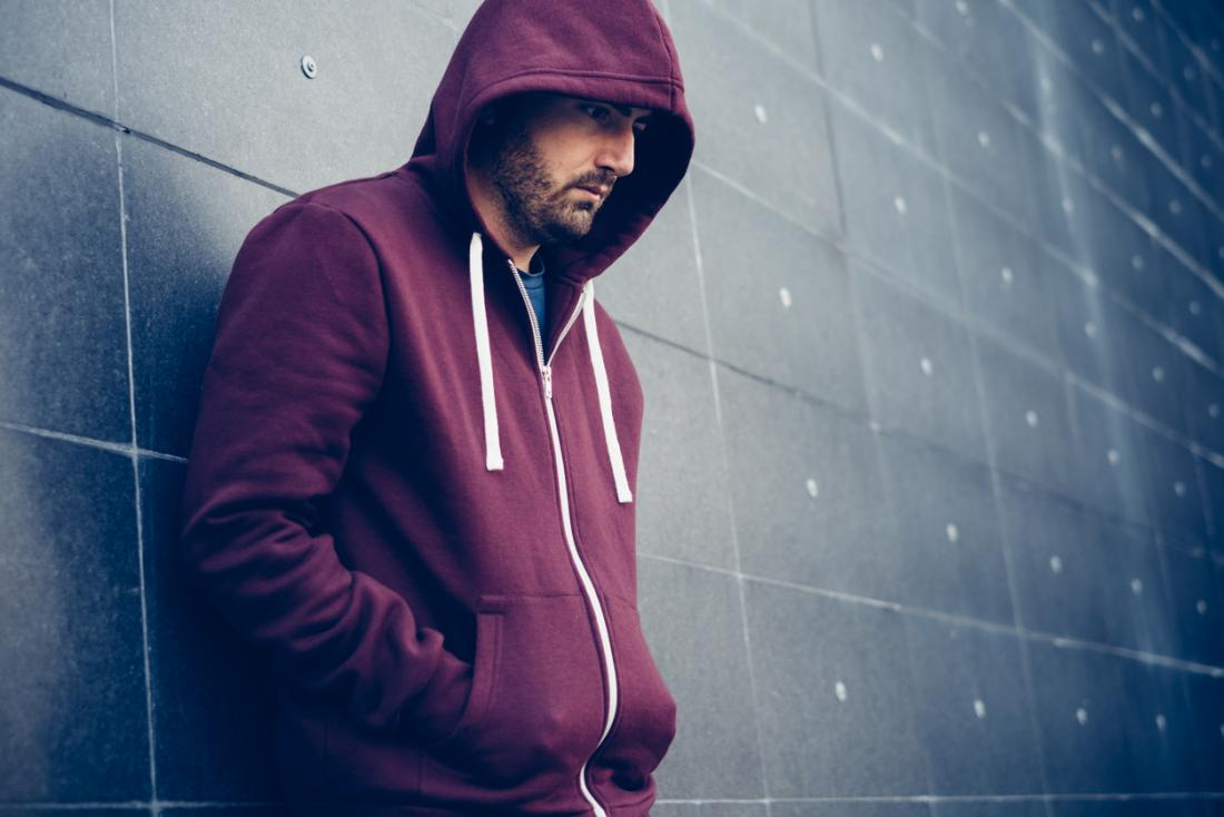 Man leaning against wall with hoodie up.
