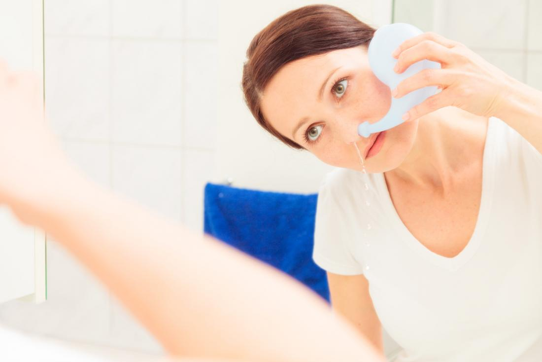 Woman using a Neti pot to clear her nose of congestion.