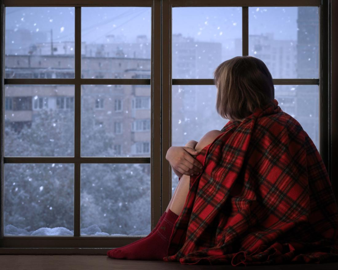girl looking out the window at the snow