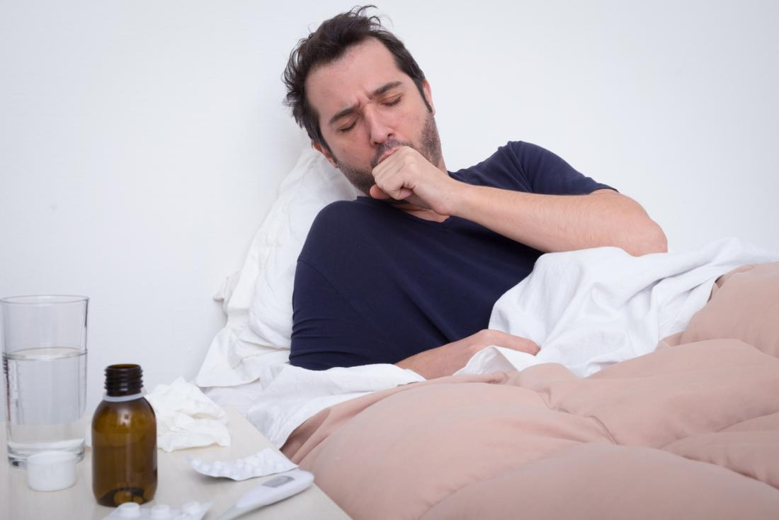Man in bed coughing, experiencing pneumonia.