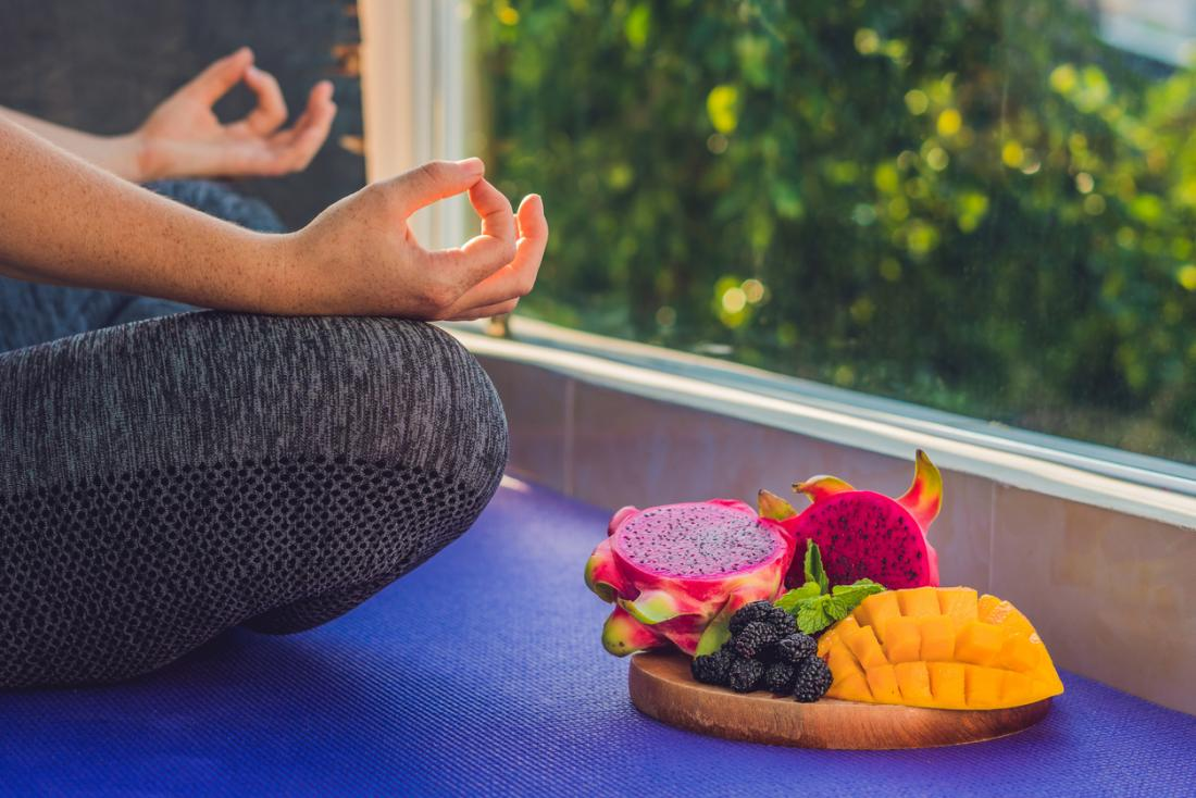 woman meditating and plate of fruit