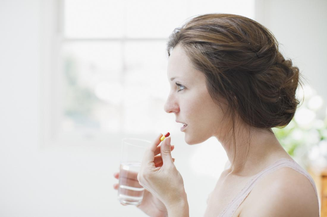 Woman looking into mirror while taking pills.
