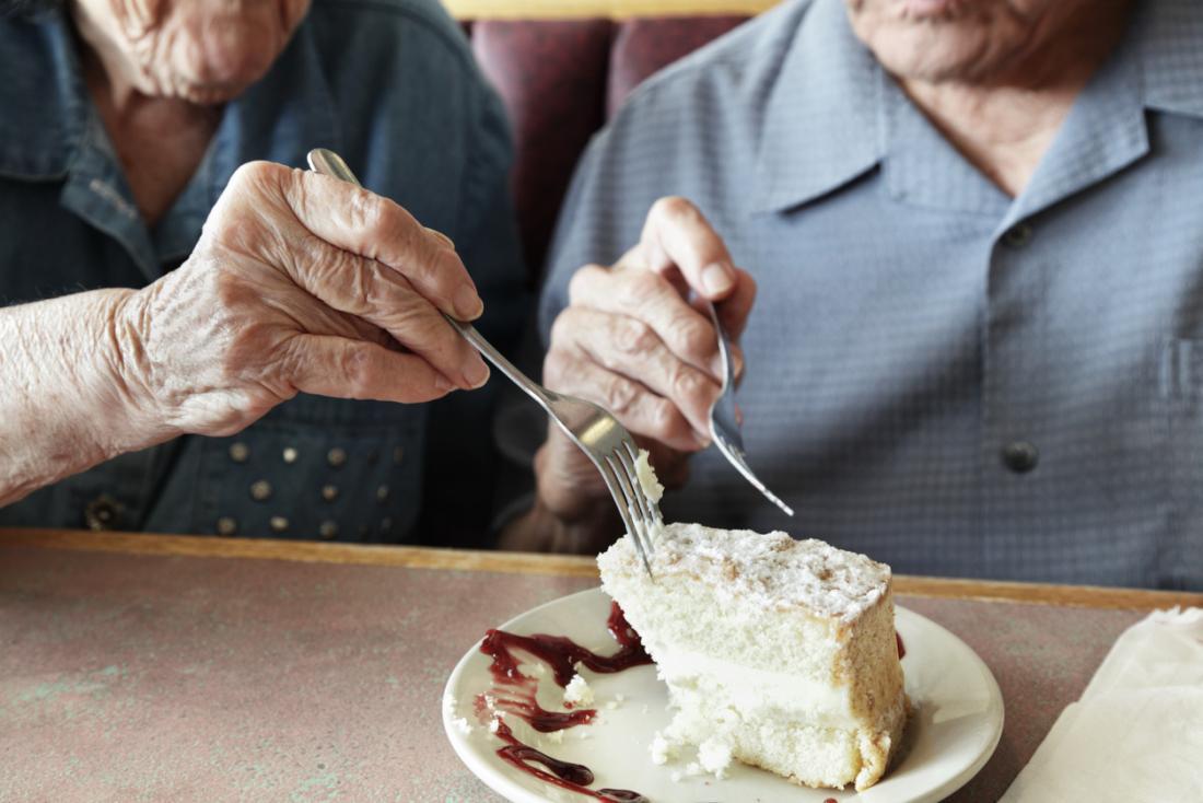 un couple plus âgé mangeant une part de gâteau