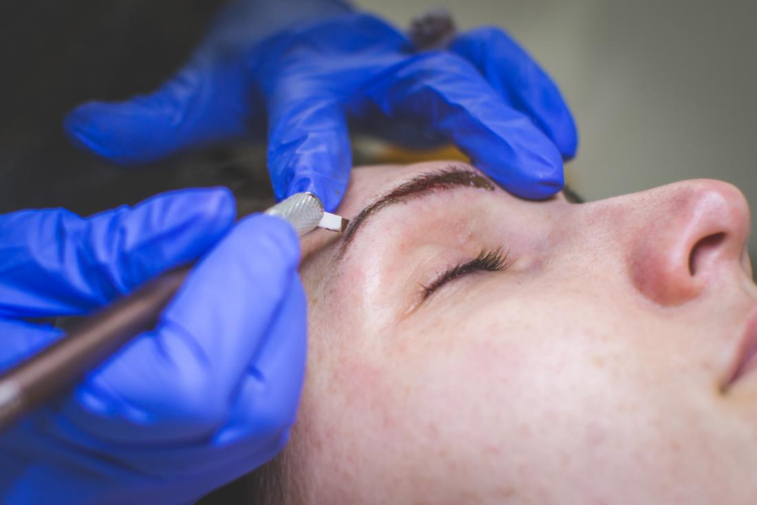 Microblading cosmetic tattooing procedure for eyebrows.