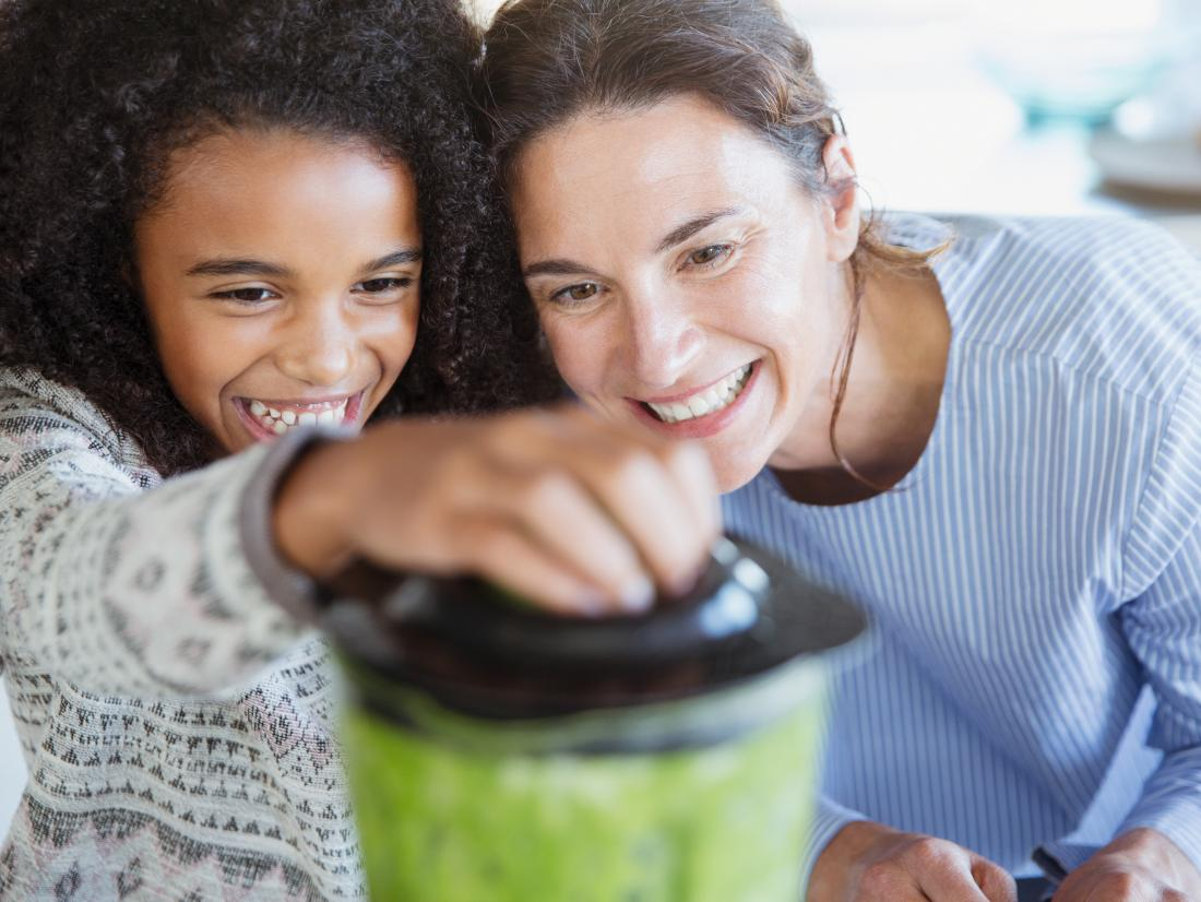 a mother and daughter making a green smoothie in a blender.