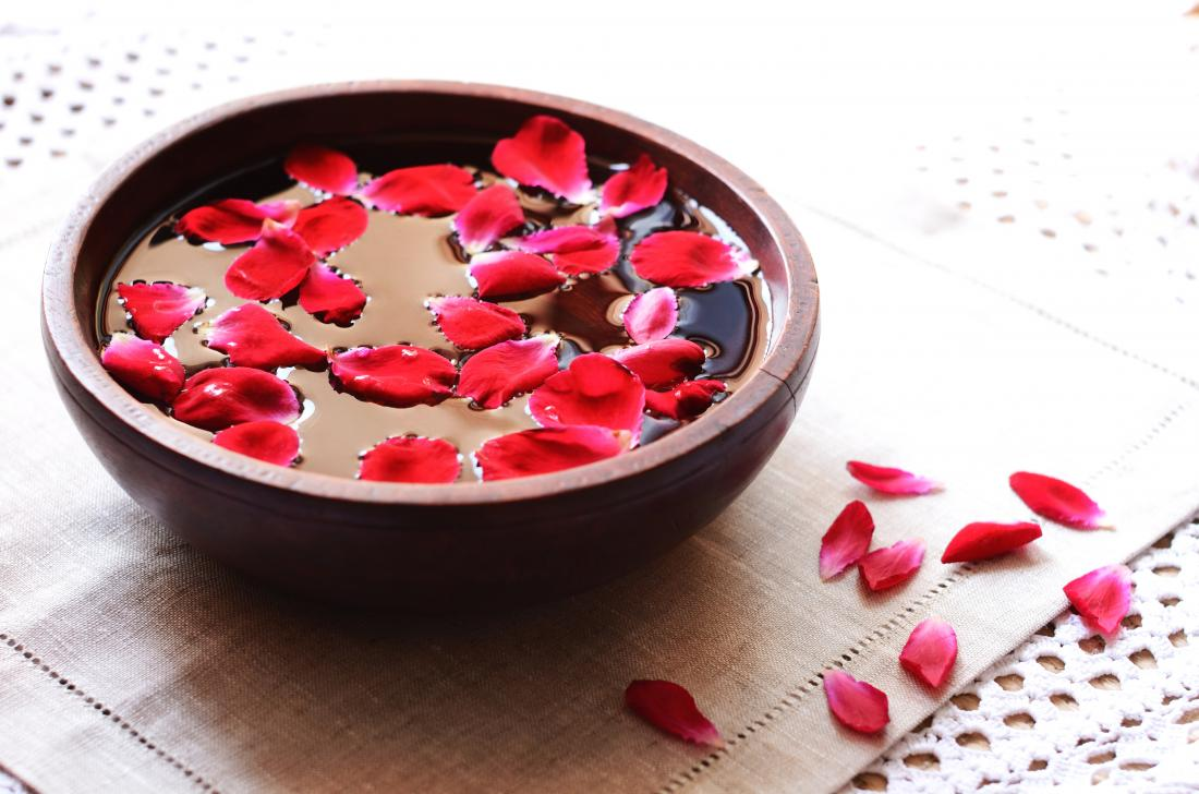 Rose water in a bowl with rose petals, for vapor therapy.