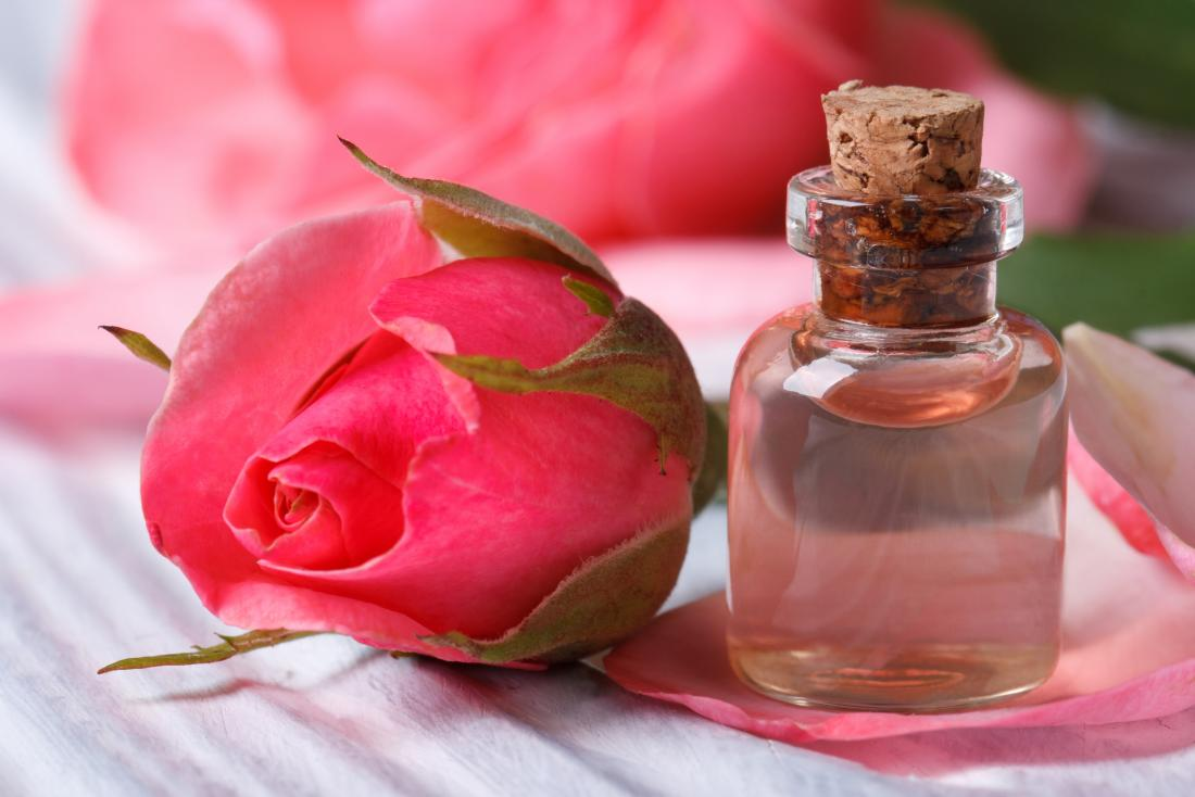 Rose water in small glass bottle, next to rose flower.