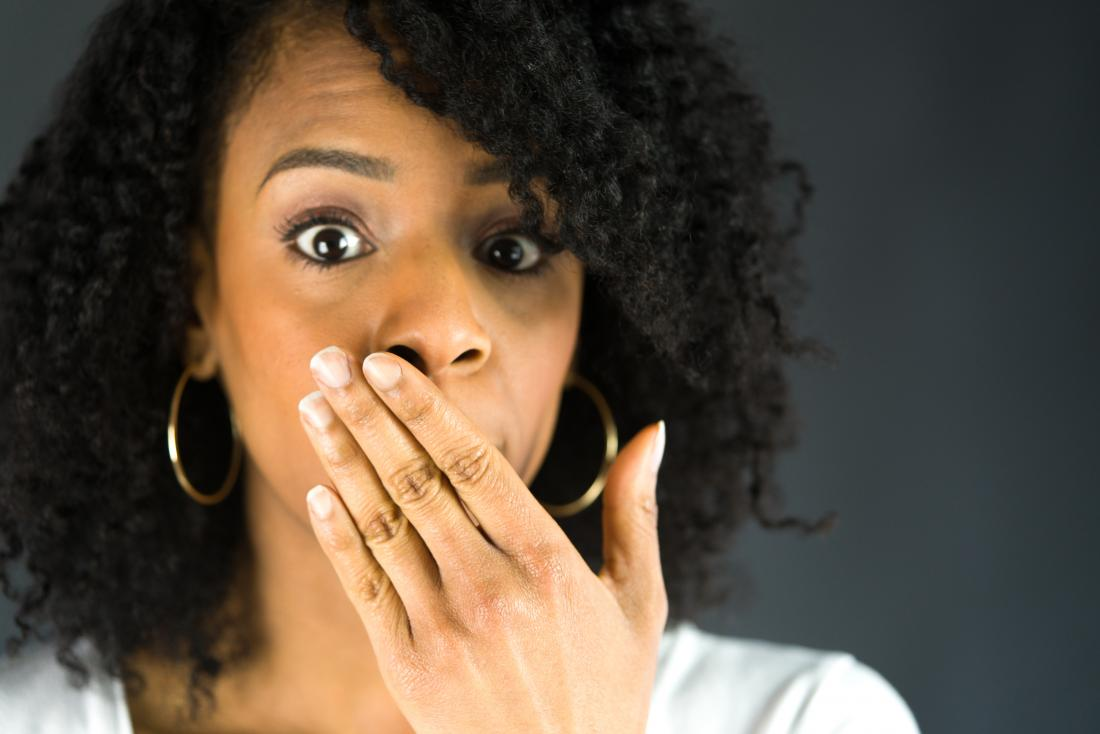woman covering her mouth with one hand