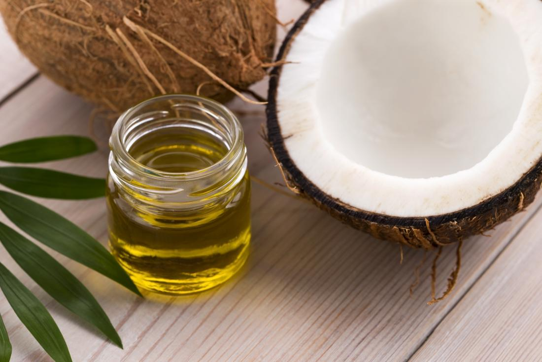 MCT oil from coconuts in glass jar, with halved coconut and leaves.
