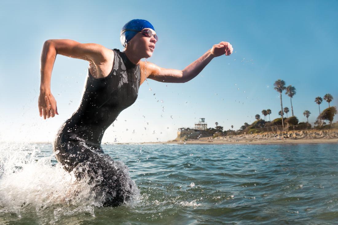 Muskulöser weiblicher Schwimmer, der in einem Triathlon, aus Meer heraus laufend konkurriert.
