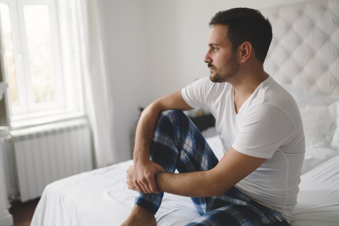 Man sitting on a bed looking contemplative, suffering from erectile dysfunction, or ed.