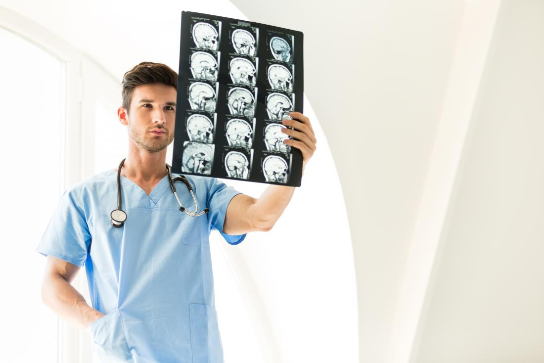 young male doctor examining brain scans