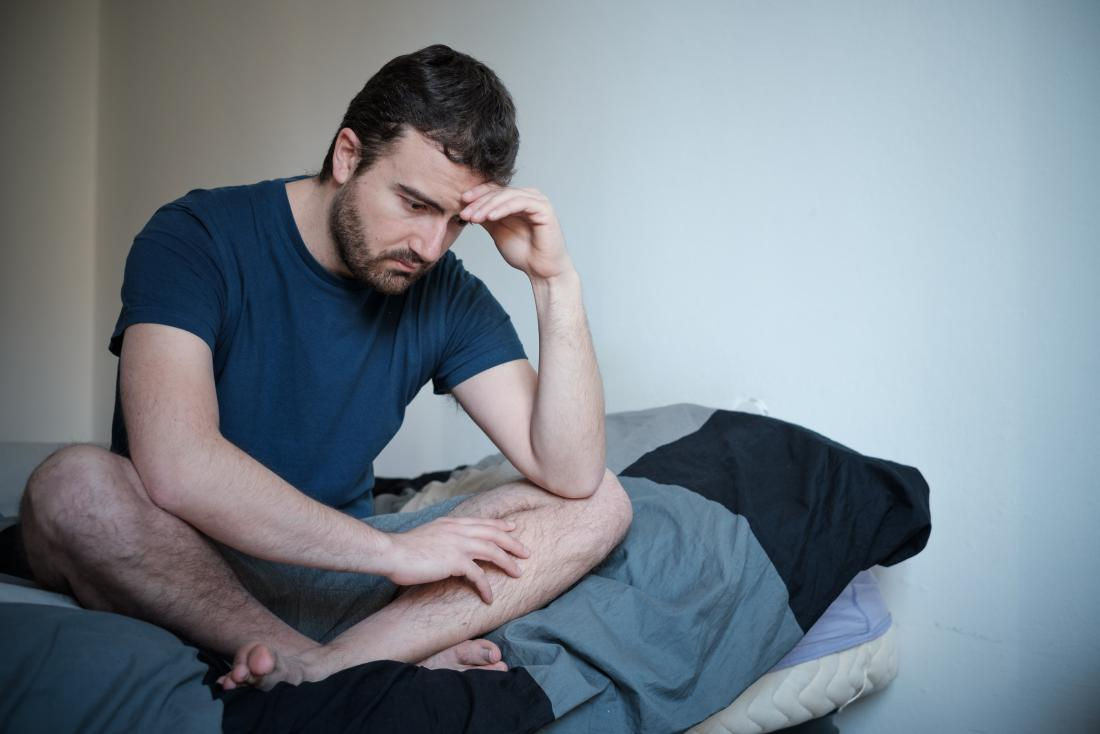 Depressed and anxious man sitting cross-legged on bed.