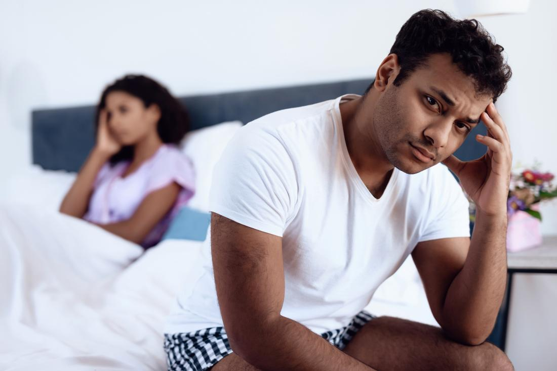 Man and woman in bed looking upset, having sexual intimacy problems.