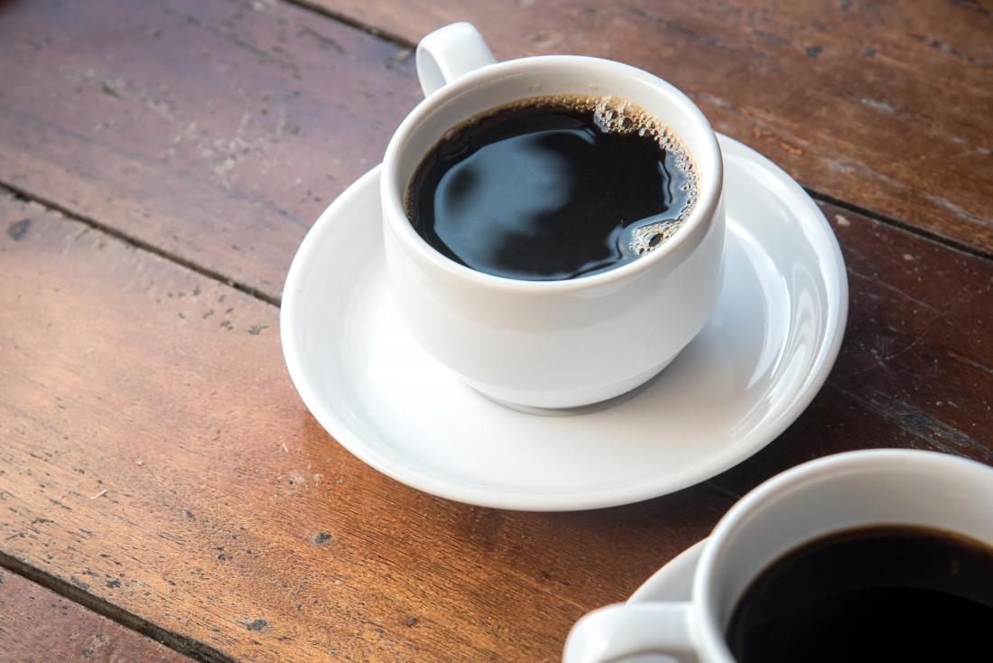 Black coffee in mugs and saucers on wooden table.