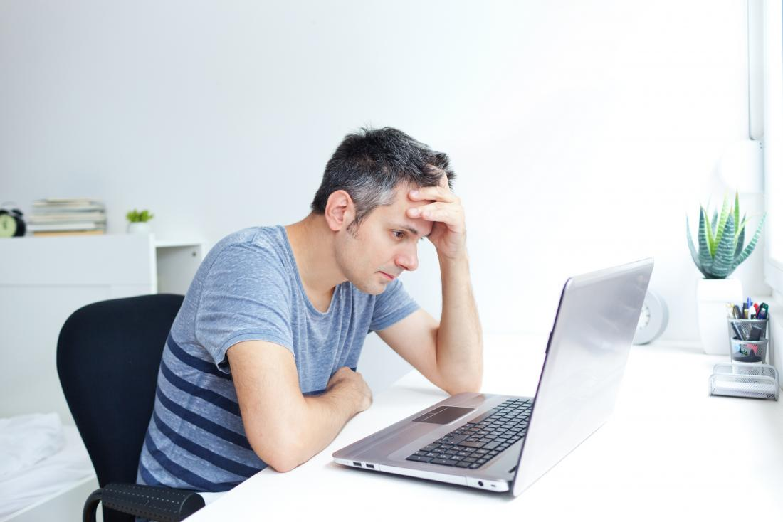 Stressed man working on laptop with white and gray hair