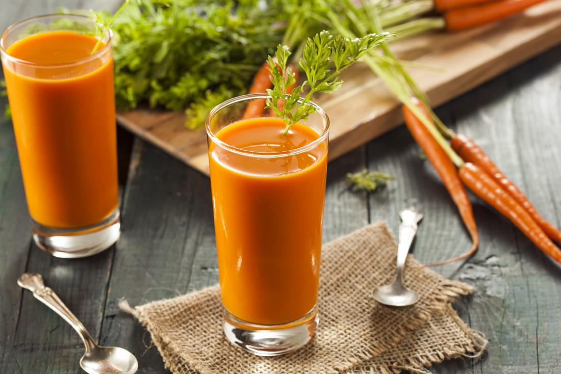 Carrot juice in glasses next to raw carrots on chopping board.