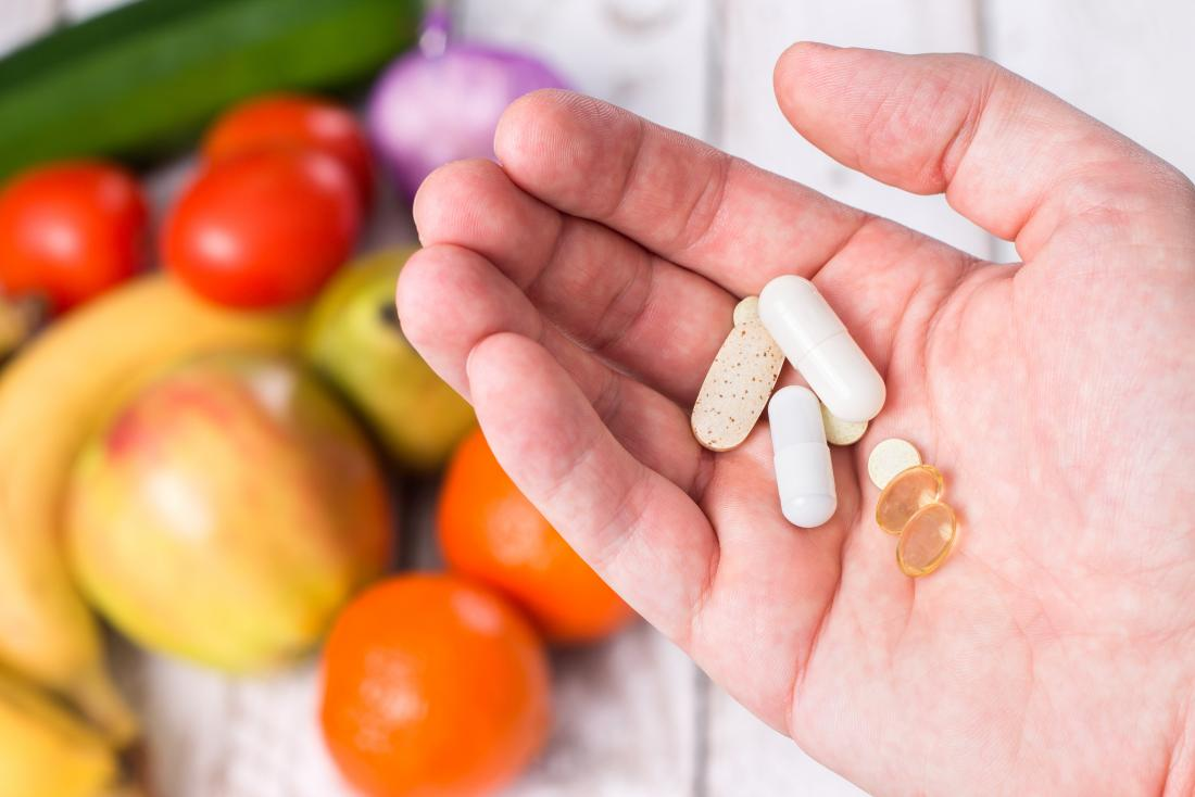 Person holding fat-soluble vitamin supplements over array of fruit and vegetables.