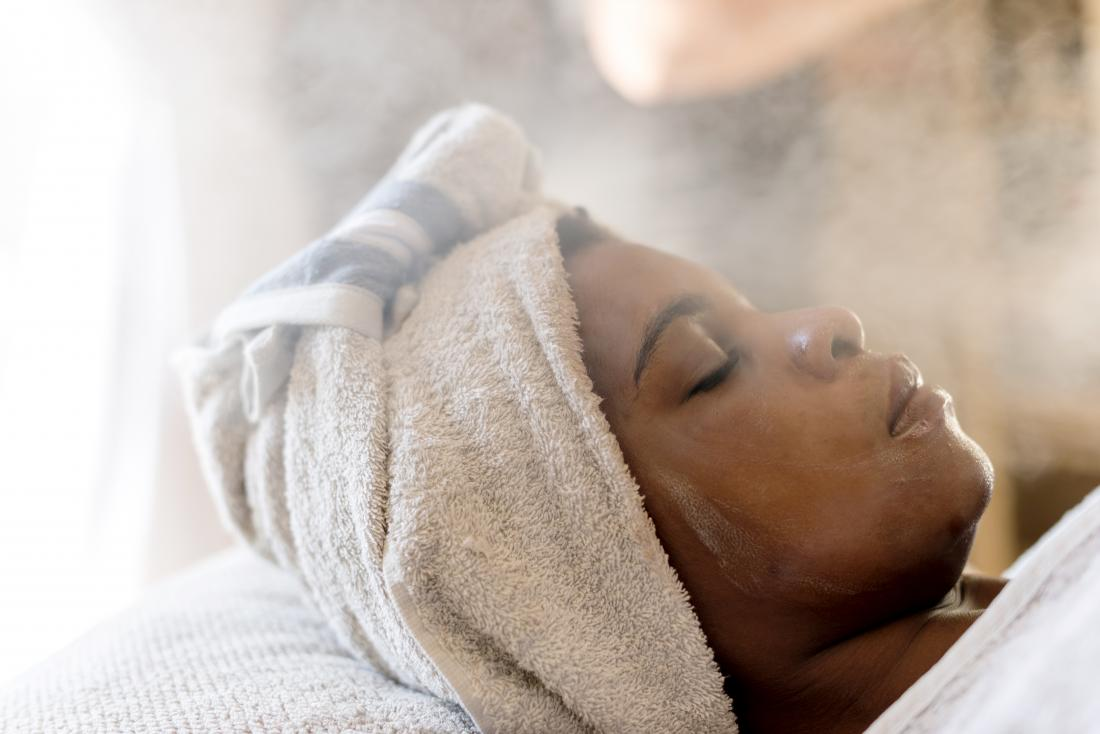 Woman receiving steam therapy spa treatment to improve facial skin.