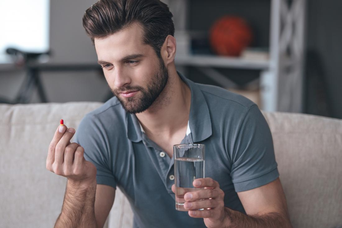 man holding a red pill and a glass of water