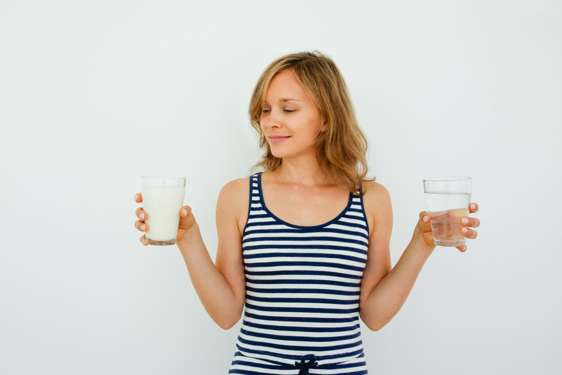 young woman holding a glass of milk in one hand and a glass of water in the other