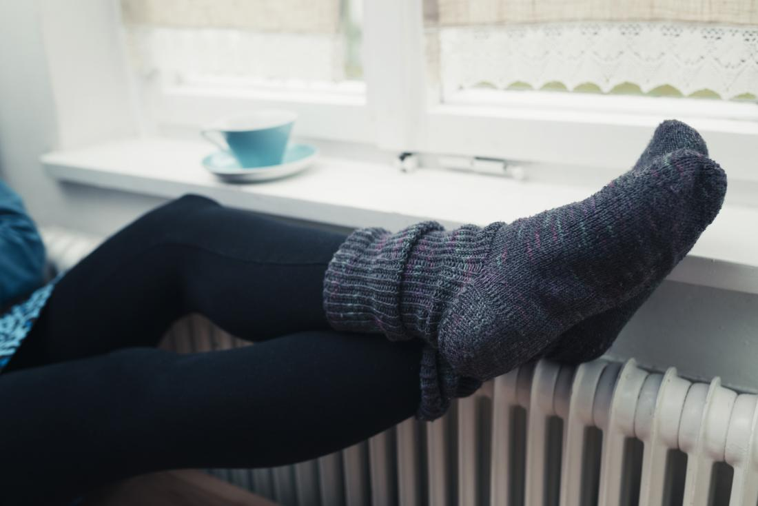 Person with thick winter socks on cold feet, perched on top of radiator heater.