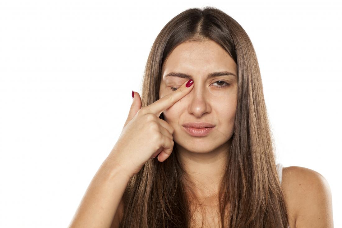 woman touching her eye