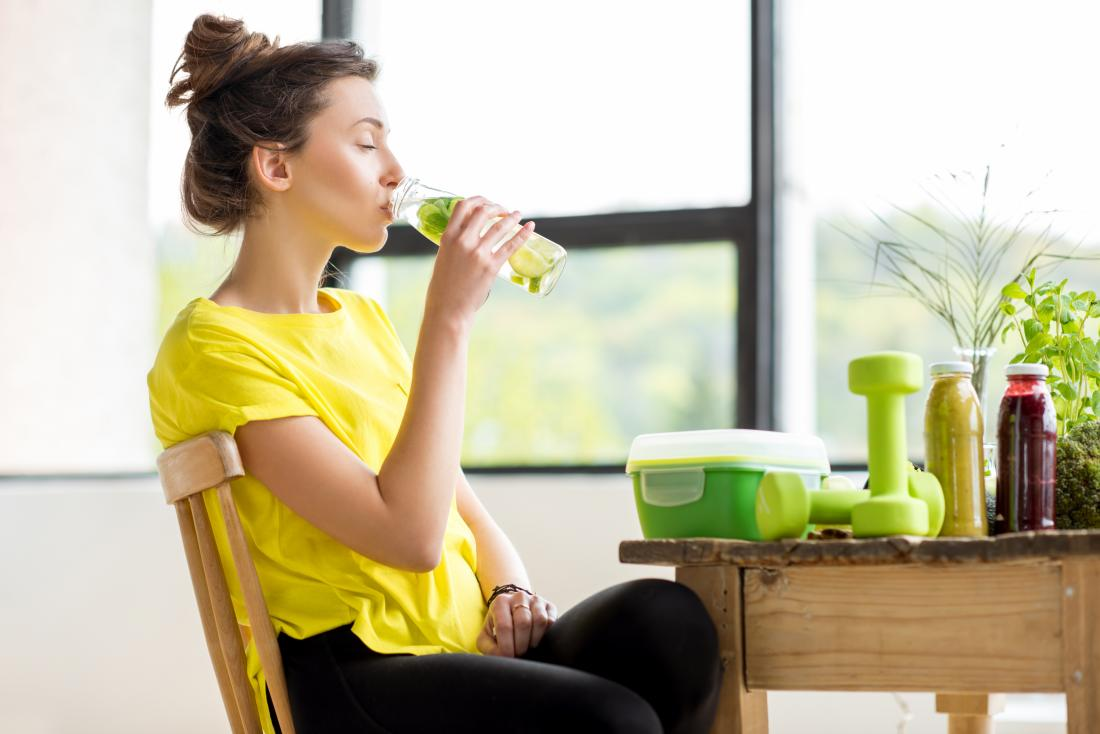 Woman sitting at table in fitness sports clothes, with dumbbell weights on table, with cleansing juice and lemon water.