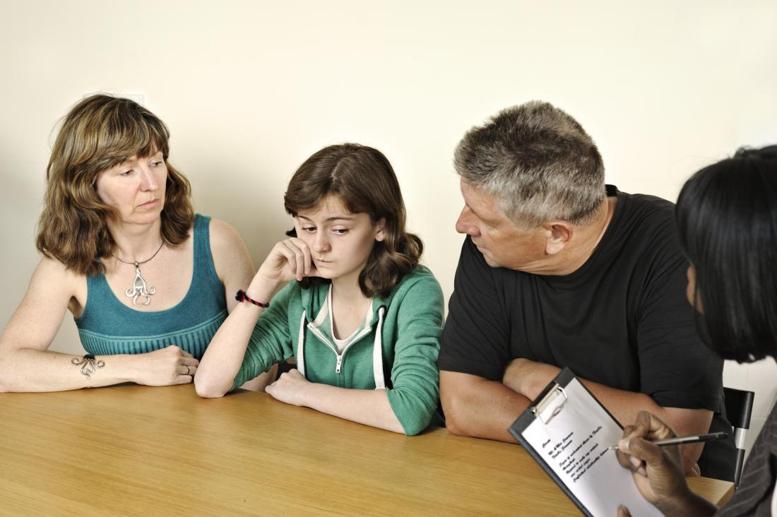 parents attending counselling session with daughter