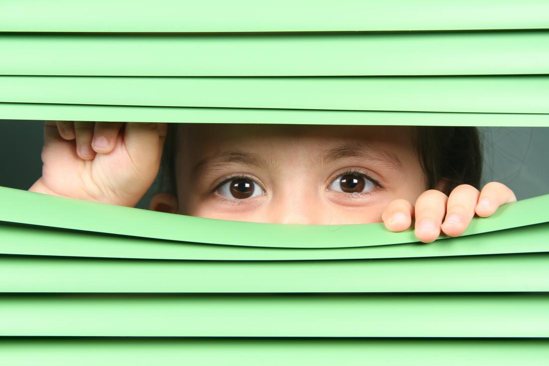 Child looking through blinds